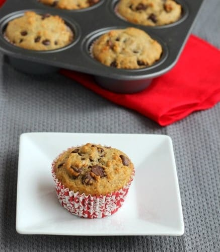 Overhead view of muffin on plate with muffins in tin in the background.