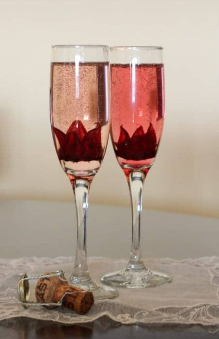 Front view of 2 champagne flutes filled with hibiscus brunch cocktails, on lace cloth, with champagne cork.