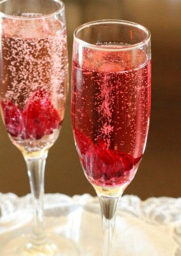Close up of hibiscus cocktail in stemmed champagne glass.