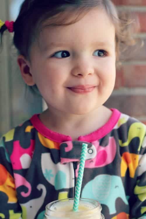 Closeup of toddler girl looking into distance with small smile, holding smoothie.