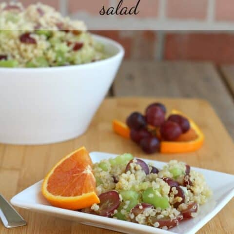 Quinoa salad on small square white plate garnished with half slice of orange.