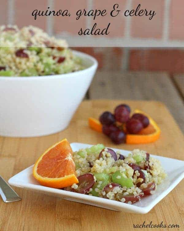 "Quinoa salad on small square white plate garnished by half slice of orange. Large salad bowl in background. Text overlay reads ""quinoa, grape & celery salad, rachelcooks.com"""