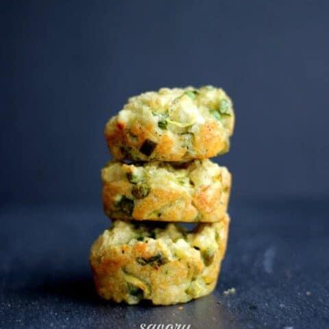 Stack of three muffins on dark gray surface.