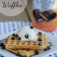 "Square white plate containing two waffles, garnished with whipped cream and chocolate chips. In the background is a bottle of creamer. Text overlay reads ""Heath Waffles."""