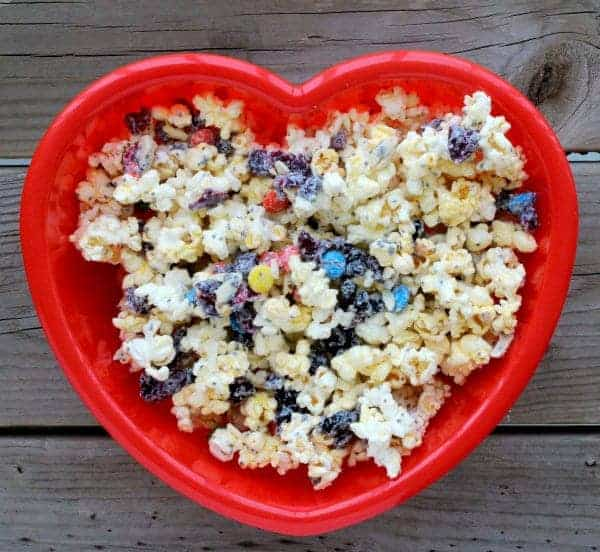 Overhead of red heart shaped bowl containing popcorn snack mix.