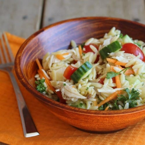 Single serving of salad in wooden bowl on orange placemat.