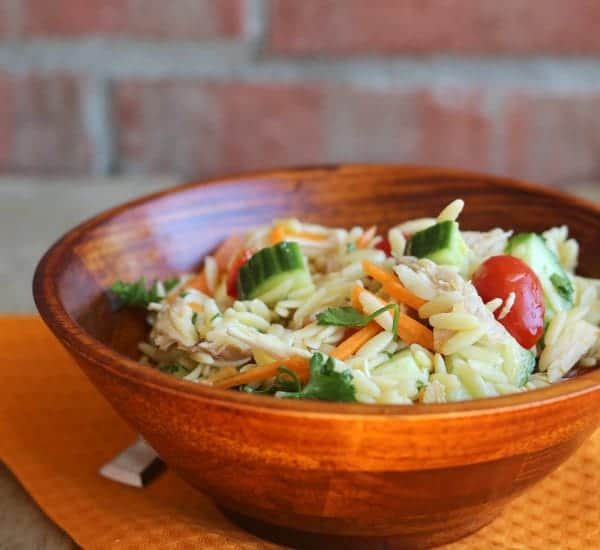 Front view of salad in wooden bowl, on orange placemat.