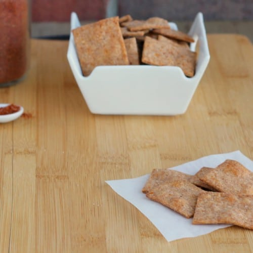 A handful of crackers on small white paper, with bowl full in background.