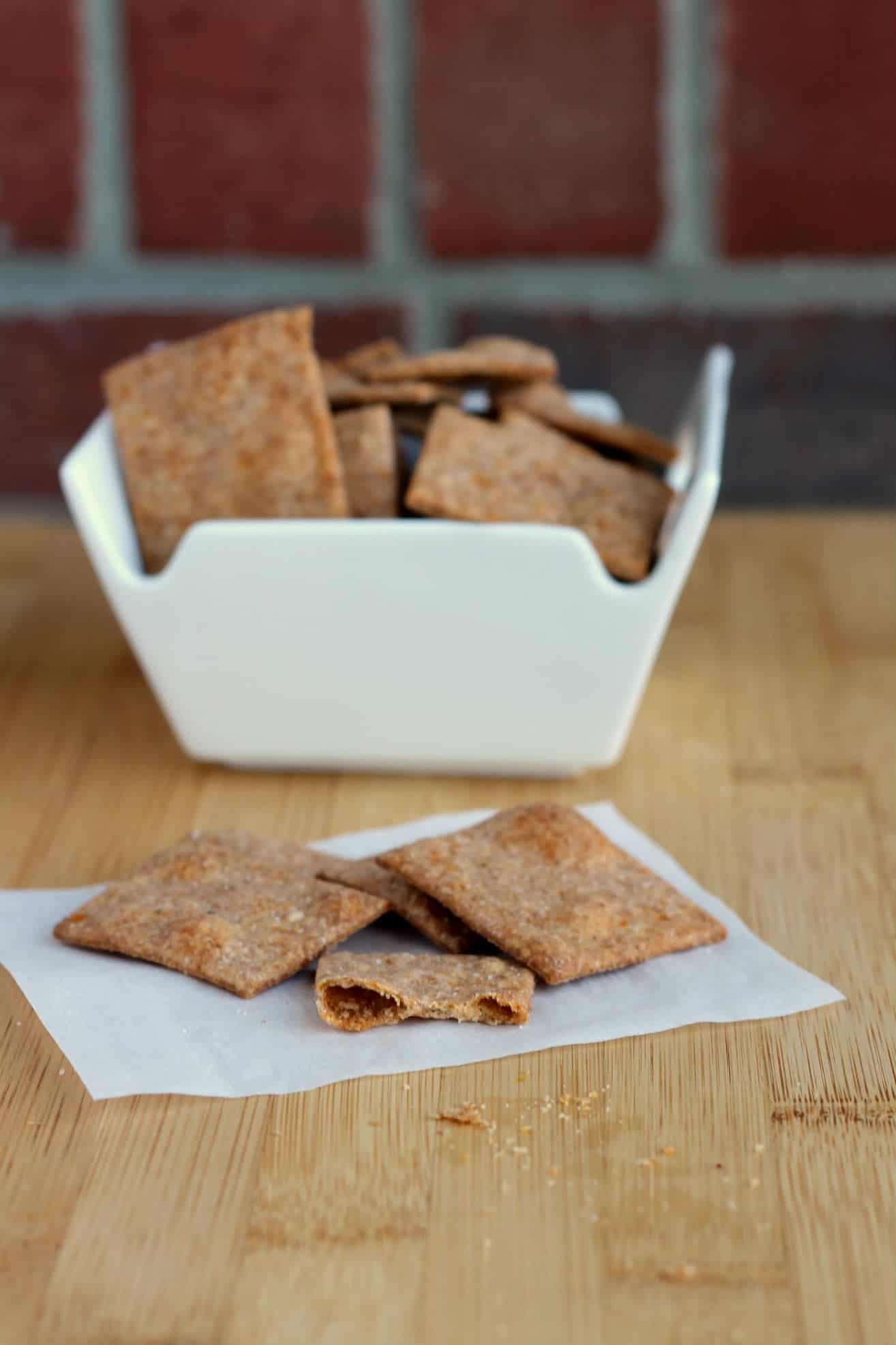 A handful of crackers on white paper with a bowl of wheat thins in background.