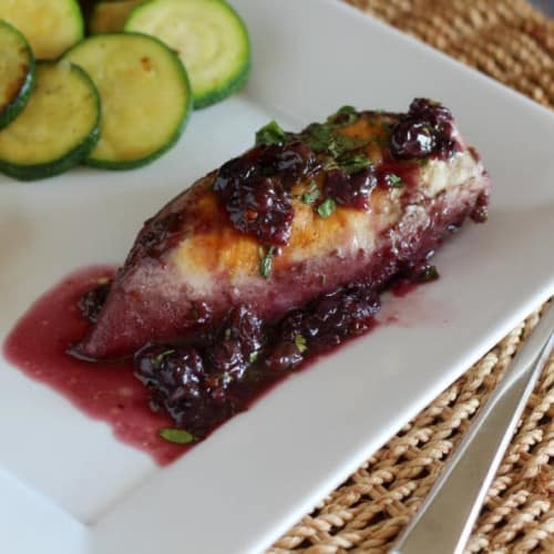 Chicken with sauce on white plate with zucchini slices.