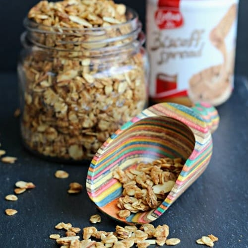 Front view of colorful scoop with granola spilling out, jar of granola and container of Biscoff Spread in the background.