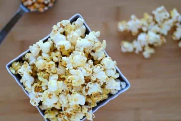 Overhead of cool ranch popcorn in square container.