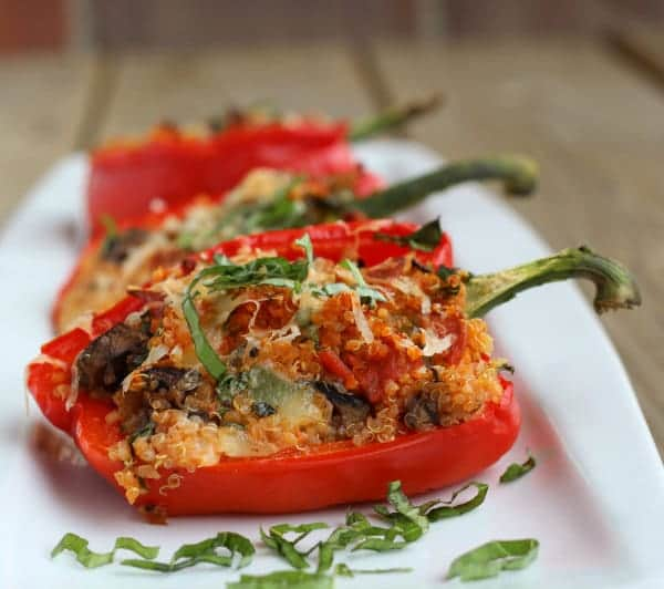 Close up image of half of a red bell pepper stuffed with pizza sauce, quinoa, mushrooms, mozzarella cheese. It is garnished with fresh basil leaves.