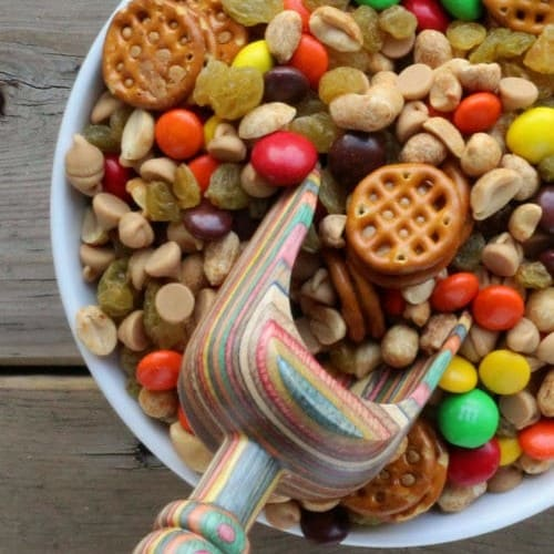 Partial image of large bowl containing trail mix with scoop inserted.