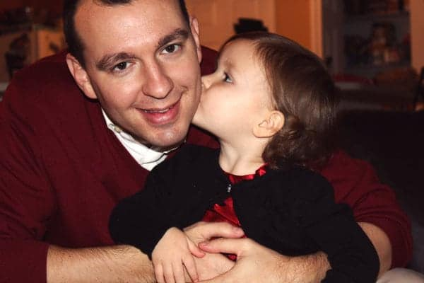 Child on father's lap, kissing him on cheek.