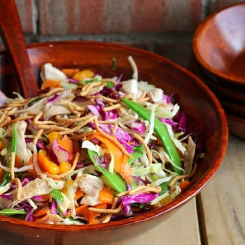 Salad in wooden bowl with wooden spoon inserted.