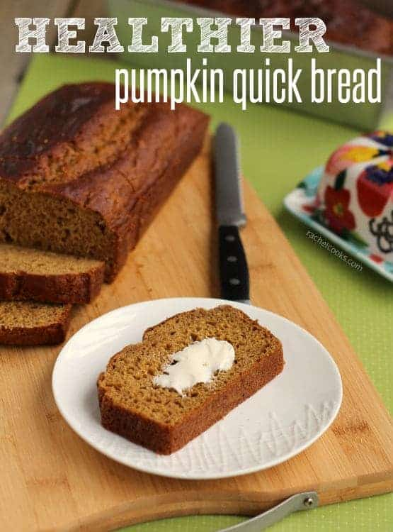 Front view of a small white plate containing a slice of pumpkin bread with butter, on a wooden cutting board with a sliced loaf of bread and bread knife. Text overlay reads 'healthier pumpkin quick bread.""