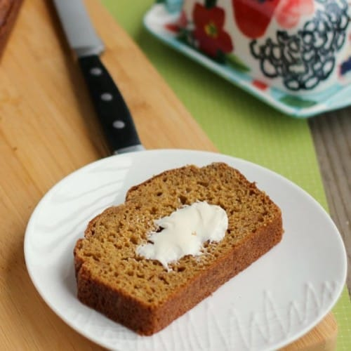 Overhead view of a slice of pumpkin bread on round white plate.