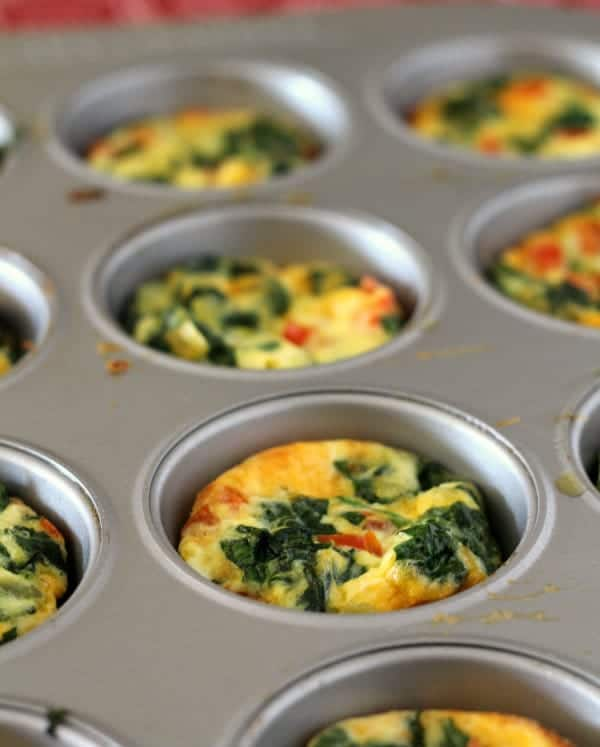 Close up image of an egg, spinach, and red pepper frittata in a muffin tin.