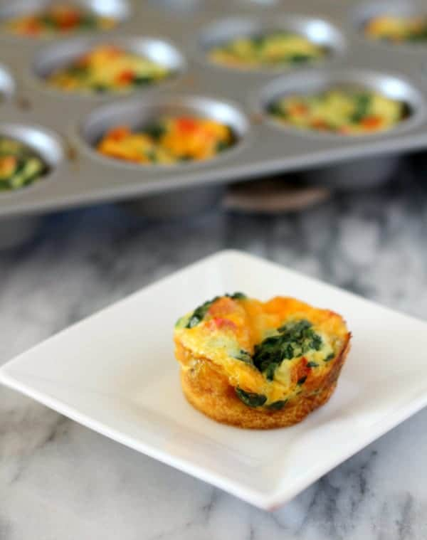 Image of a small muffin tin frittata o a small square white plate. A muffin tin full of more frittatas is pictured in the background.