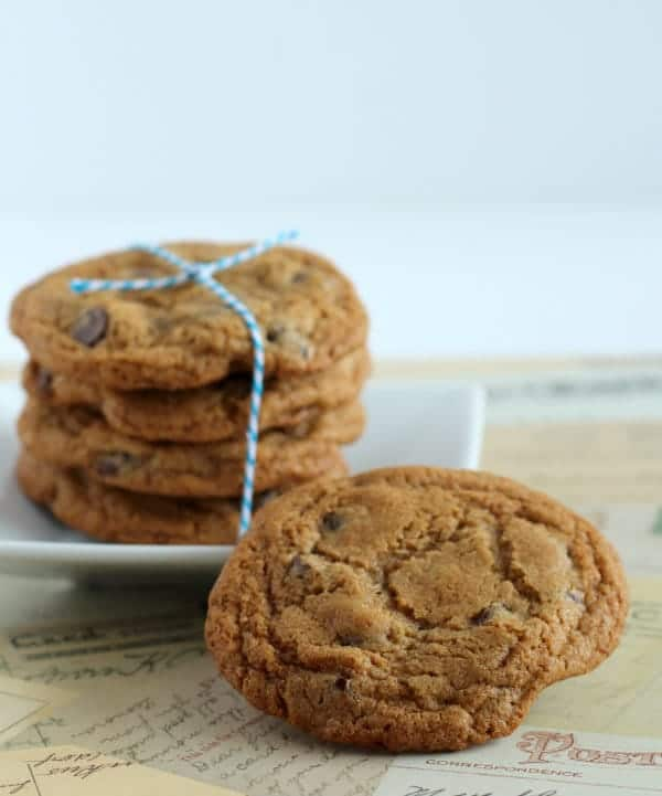 Stack of four cookies tied with string, on square white plate, with one cookie propped against plate.