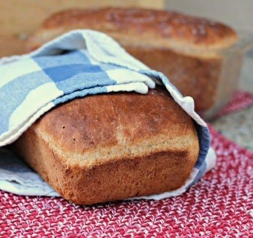 Loaf of bread wrapped in cotton towel, with another loaf in background.