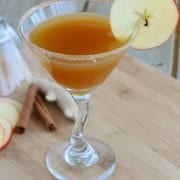 Stemmed martini glass with apple cider fake-tini, garnished with a slice of apple.!