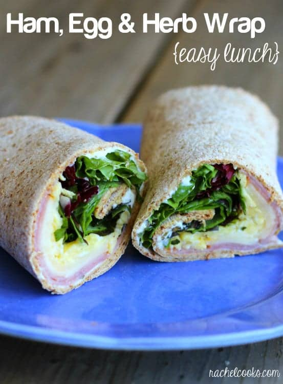 Image of a wrap on a blue plate, filled with ham, egg, cheese, greens, and cream cheese.
