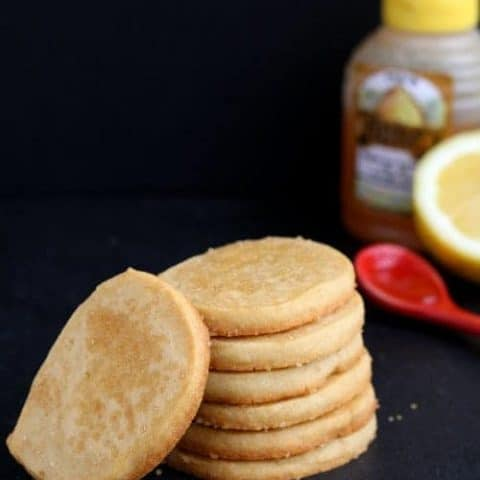 Stack of honey lemon shortbread cookies with honey , cut lemon, and red measuring spoon.