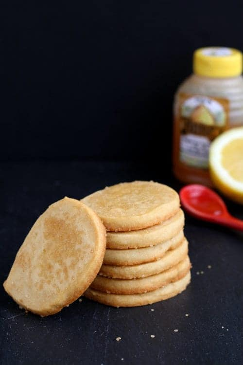 stack of several cookies on black background, with honey, lemon, and red spoon.
