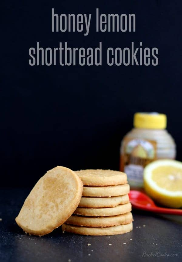 "Several cookies stacked, with cut lemon and bottle of honey, on black background. Text overlay reads ""honey lemon shortbread cookies."""