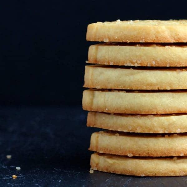 Stack of 7 honey lemon shortbread cookies, on black background.