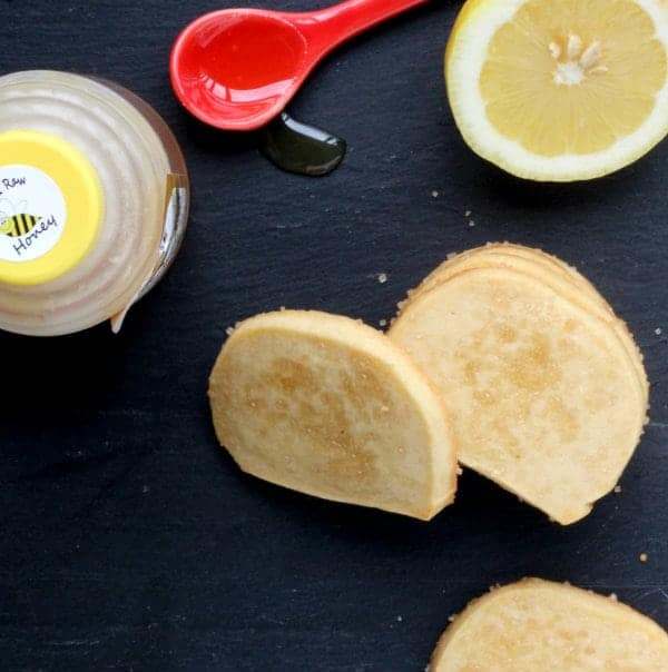 Overhead view of several cookies, cut lemon, honey jar, and red measuring spoon with honey.