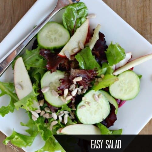 """Overhead view of tossed green salad on a plate. Text overlay reads """"easy salad with cucumbers and apples"""""""