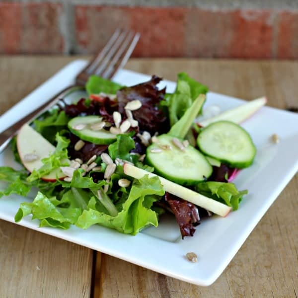 Tossed salad on white square plate. Salad contains greens, cucumbers, apples, and sunflower seeds.