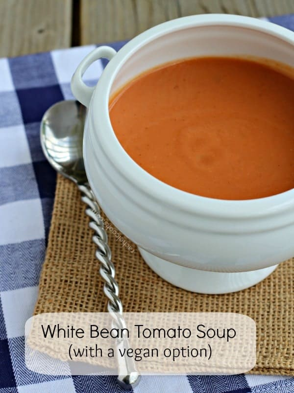 White ceramic bowl containing tomato soup, on burlap placement with decorative spoon.