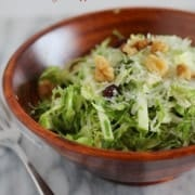 Brussels sprouts salad in a round wooden bowl, on white marble background.
