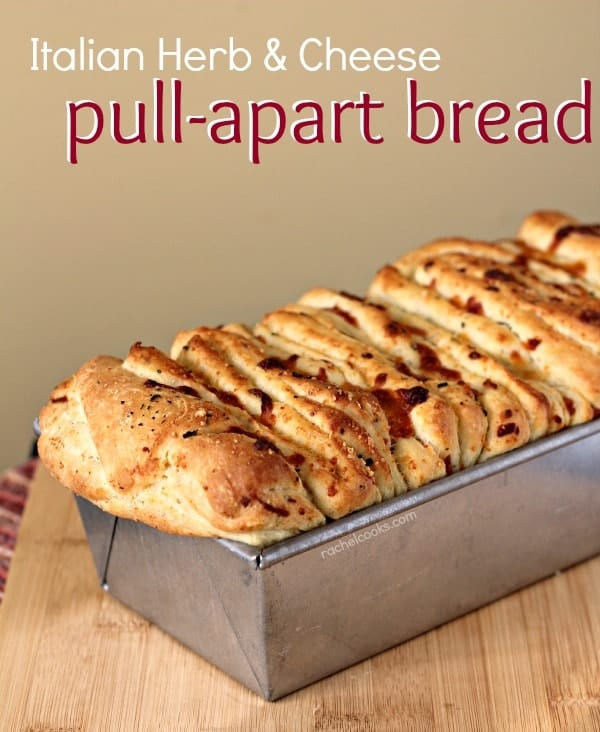 "Front view of loaf tin containing pull-apart bread, on wooden cutting board. Text overlay reads, ""Italian herb & cheese pull-apart bread."""