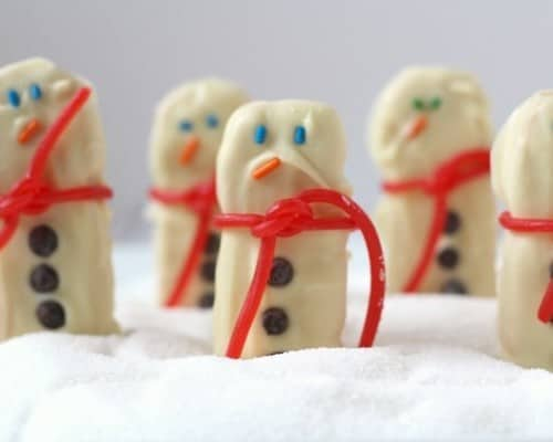 Decorated snowman cookies standing upright in artificial snow.