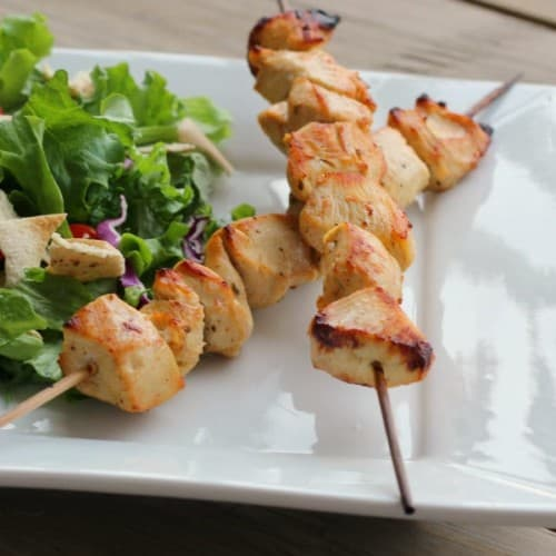 Two skewers with grilled chicken along with salad on square white plate.