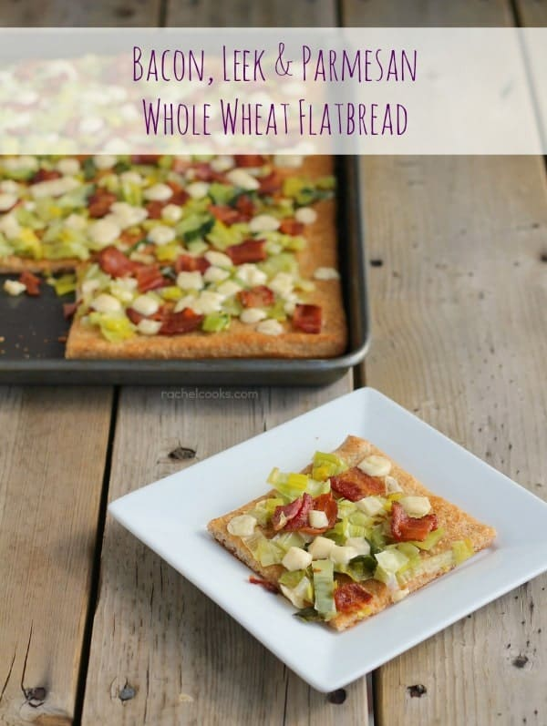 """Front top view of flatbread slice on square white plate, with flatbread in pan in the background. Text overlay reads """"Bacon, Leek, & Parmesan Whole Wheat Flatbread."""""""