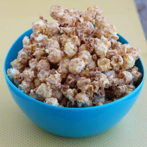 Round blue bowl holding Biscoff popcorn.
