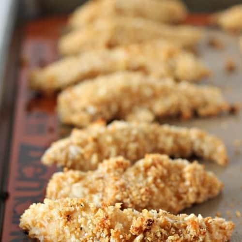Baked chicken tenders on rimmed baking sheet.