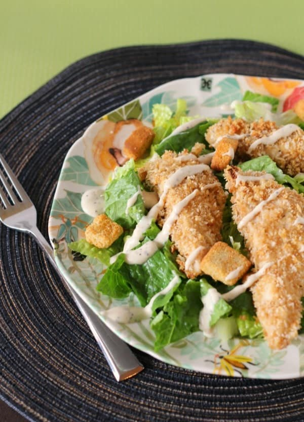 Partial image of chicken tenders served on a salad with dressing drizzled over all, on decorative plate with fork.