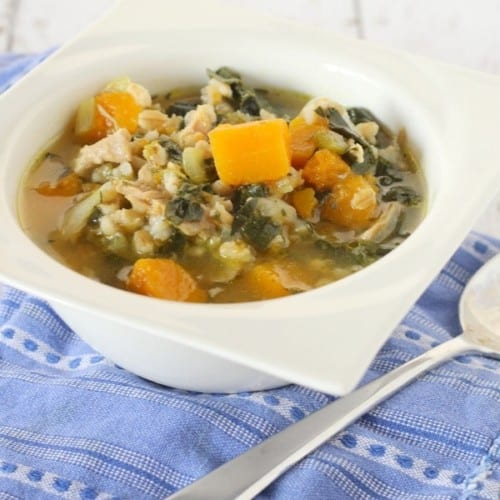 Closer view of chicken barley soup in white bowl with spoon alongside, on a blue patterned cloth.