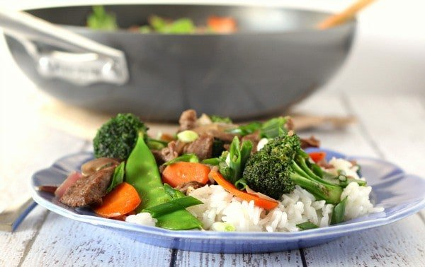 Front view of plate containing serving of beef stir fry with pan in background.