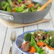 Partial image of plated beef stir fry, with non stick skillet in background.