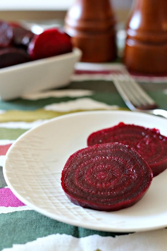 Front view of two beet slices, with dish of beets, partial wooden salt and pepper mills, fork, and patterned cloth.