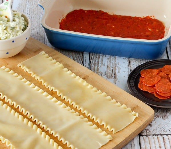 Cooked lasagna noodles on a wooden cutting board. Nearby are a bowl of cheese, a plate of pepperoni, and a blue baking dish with tomato sauce in it.