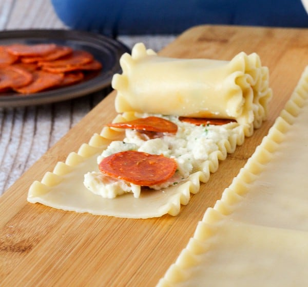 A lasagna noodle being rolled up with cheese and pepperoni inside of it.